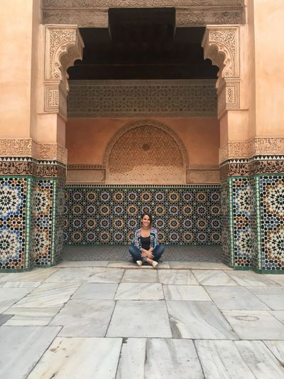 Woman Sitting Against Old Historical Building