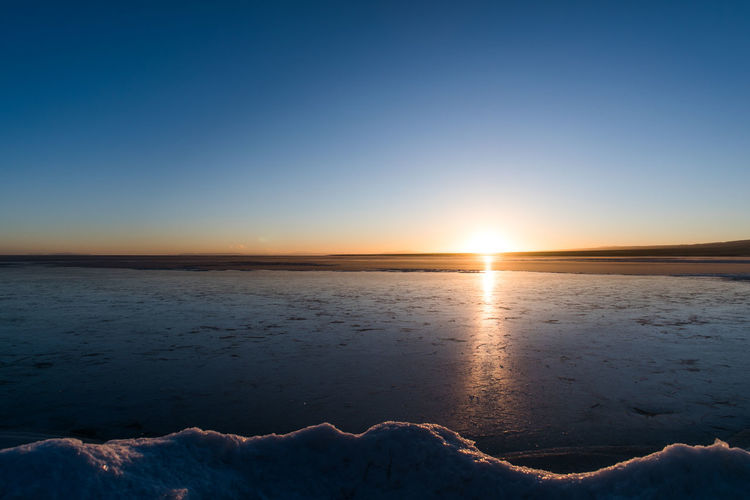 Sky Scenics - Nature Beauty In Nature Sunset Tranquil Scene Tranquility Sun No People Nature Water Idyllic Sunlight Winter Cold Temperature Copy Space Clear Sky Non-urban Scene Snow Outdoors Salt Flat