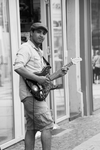 Portrait of street musician playing electric guitar on footpath