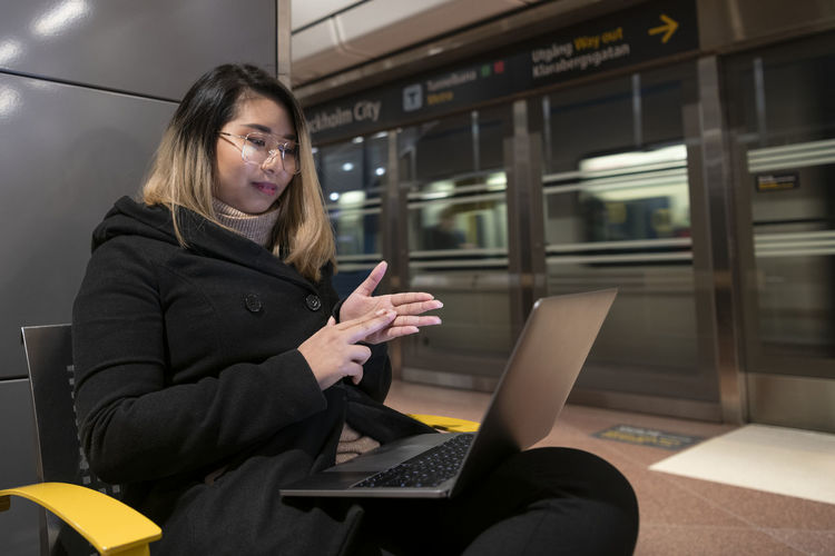 Woman using mobile phone while sitting in train