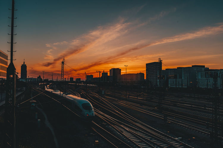 Panoramic view of railroad tracks by buildings against sky during sunset