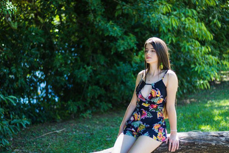 Thoughtful woman sitting on fallen tree