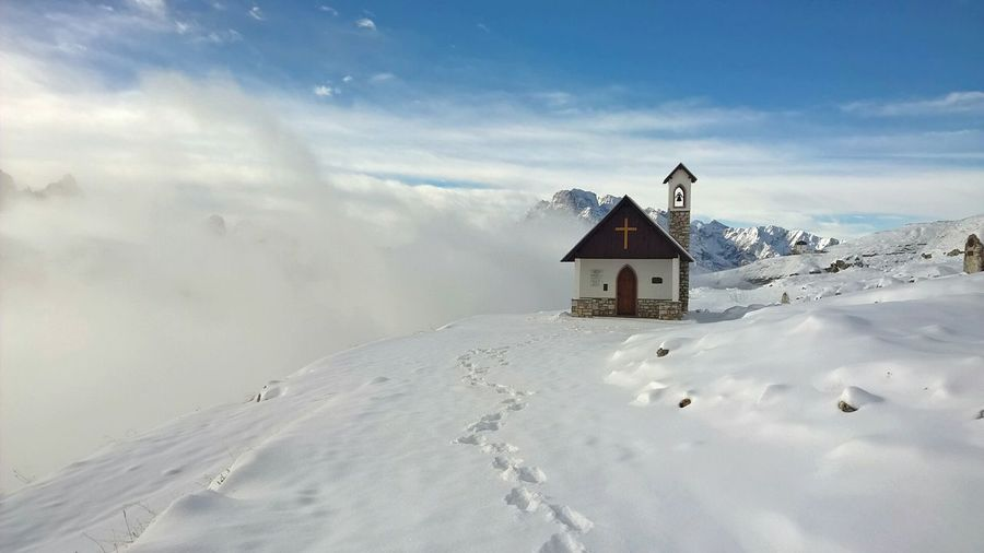 Chapel on snow covered field against sky