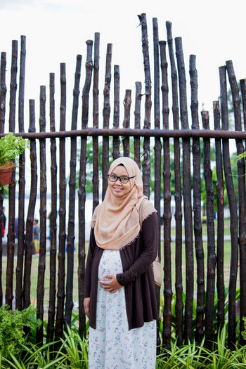 Portraiture of happy pregnant muslim woman caressing belly in park.