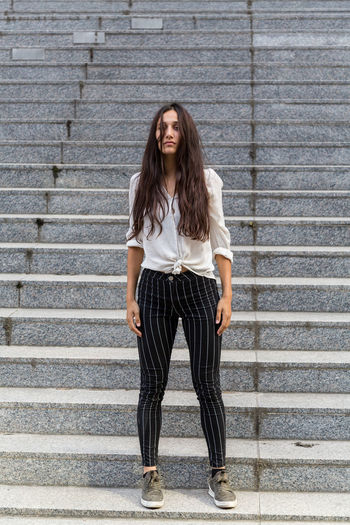 Full length portrait of a woman standing on a staircase One Person Long Hair Front View Beautiful Woman Casual Clothing Hairstyle Young Adult Front Facing Indian Mixed Race Person Young Woman Natural Lighting Looking At Camera Outdoors Full Length Staircase Brown Hair Portrait Hair