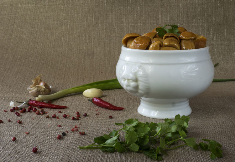 Salted mushrooms in bowl by spices on table