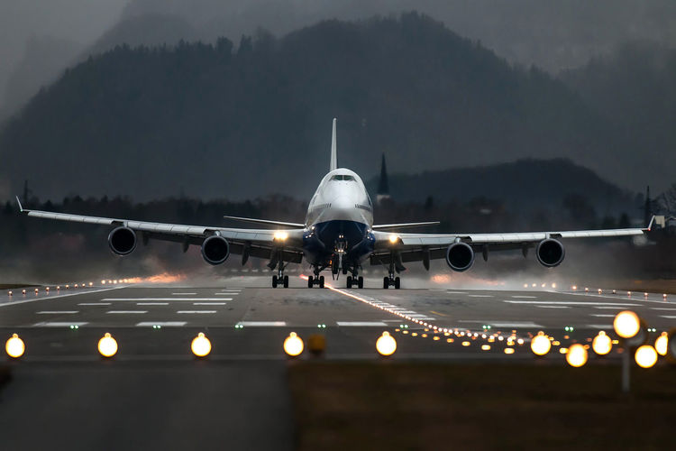 Airplane on illuminated runway against mountain range
