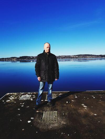 Full length of man standing on pier against blue sky