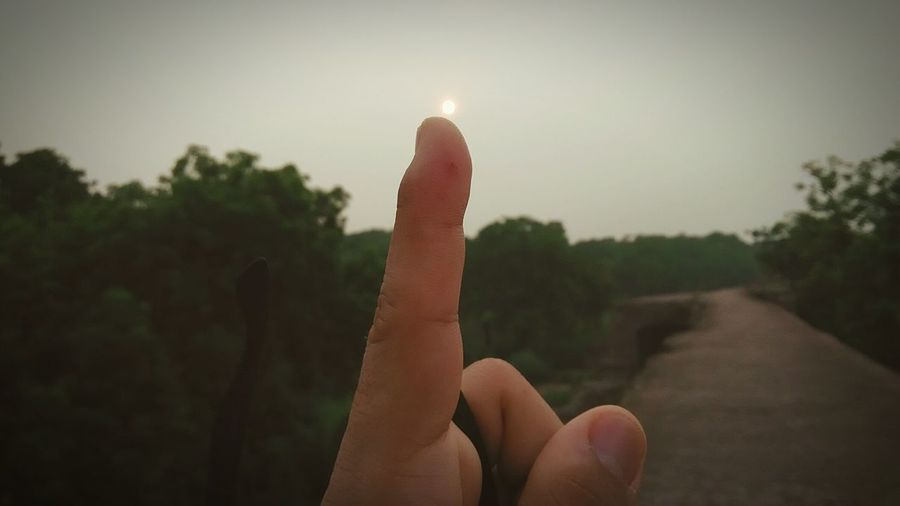 Close-up of human finger against sky