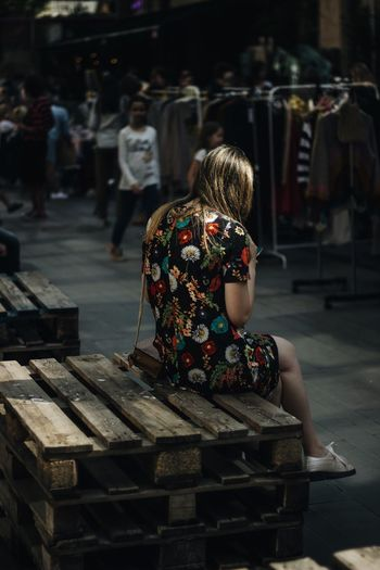 Woman wearing floral patterned dress while sitting at market