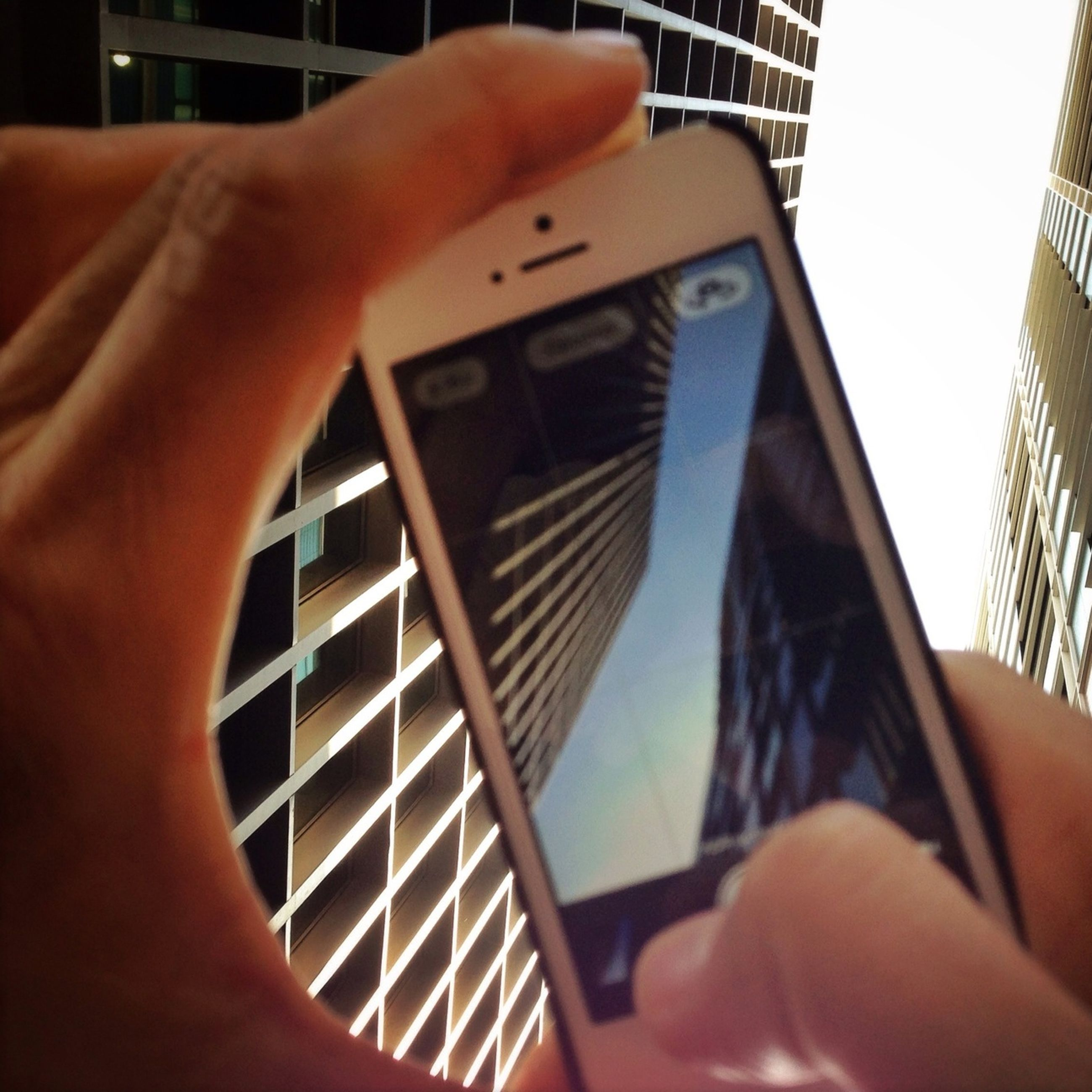 person, part of, cropped, human finger, architecture, holding, building exterior, personal perspective, unrecognizable person, built structure, lifestyles, leisure activity, modern, close-up, tower, low angle view