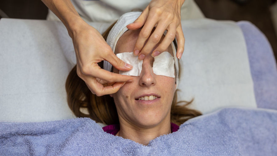 High angle view of woman putting cotton over eyes