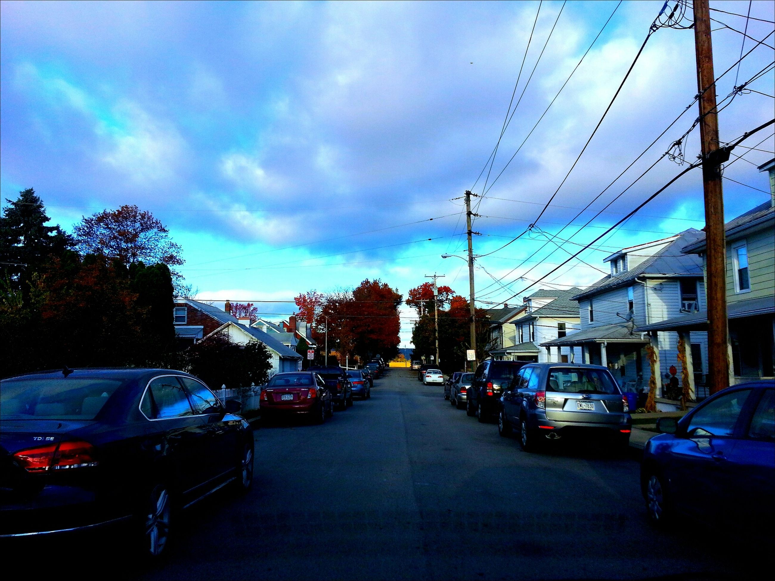 transportation, car, land vehicle, building exterior, mode of transport, architecture, street, built structure, sky, the way forward, city, road, diminishing perspective, parking, tree, city street, stationary, cloud - sky, bare tree, parked