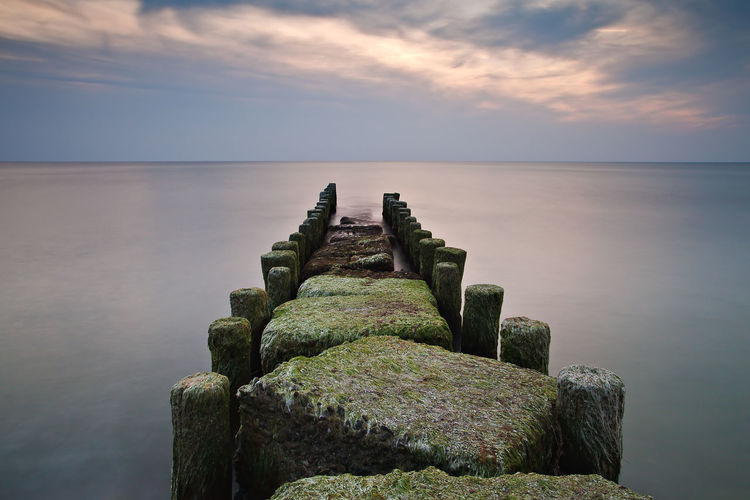 Groynes on the Baltic Sea coast. Ahrenshoop Baltic Sea Beach Beauty In Nature Calm Horizon Over Water Idyllic Landscape Moss Nature Nature Non-urban Scene Ocean Scenics Sea Seascape Shore Sky Stone - Object The Way Forward Tourism Tranquil Scene Tranquility Water Wooden Post