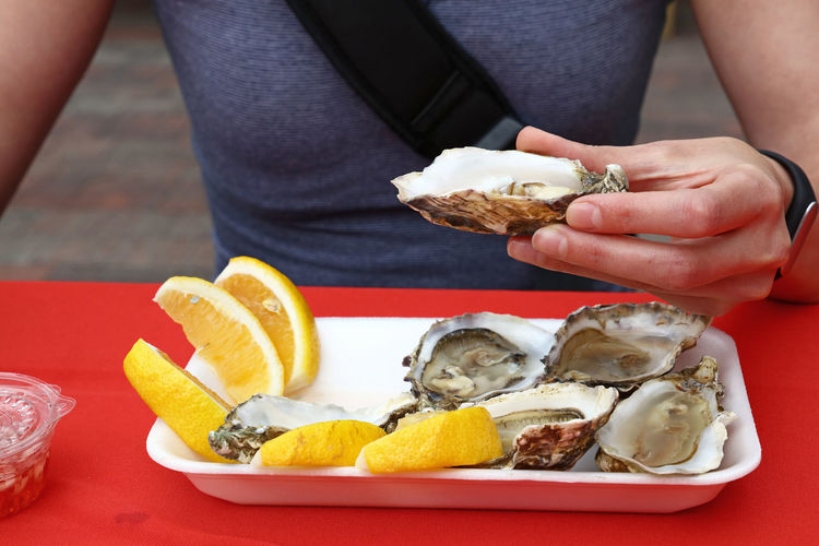 Midsection Of Man Holding Oyster In Plate
