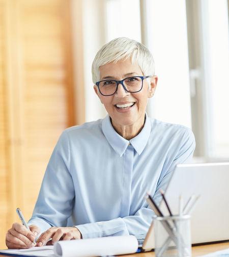 Portrait of smiling senior businesswoman writing on paper