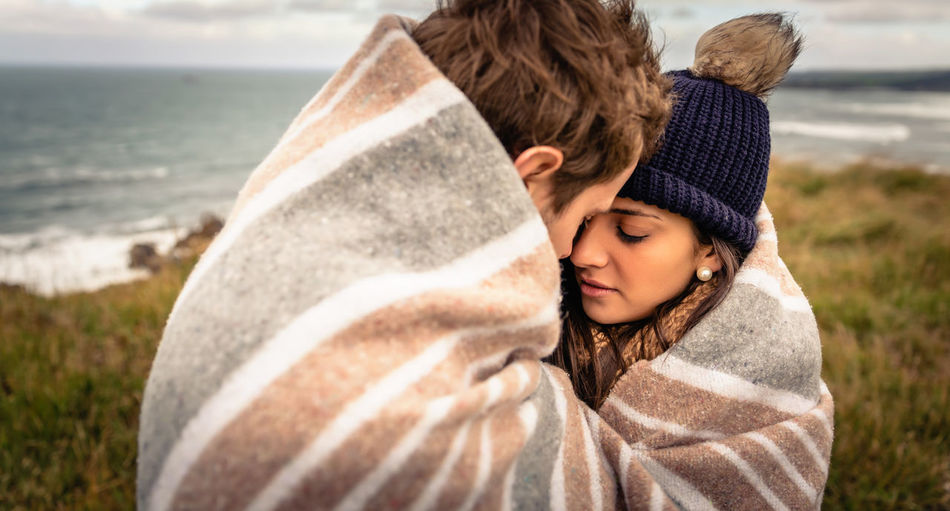 Couple Covered With Blanket Romancing By Sea On Field