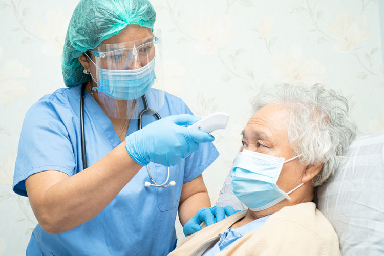 Doctor wearing mask checking temperature of patient at hospital