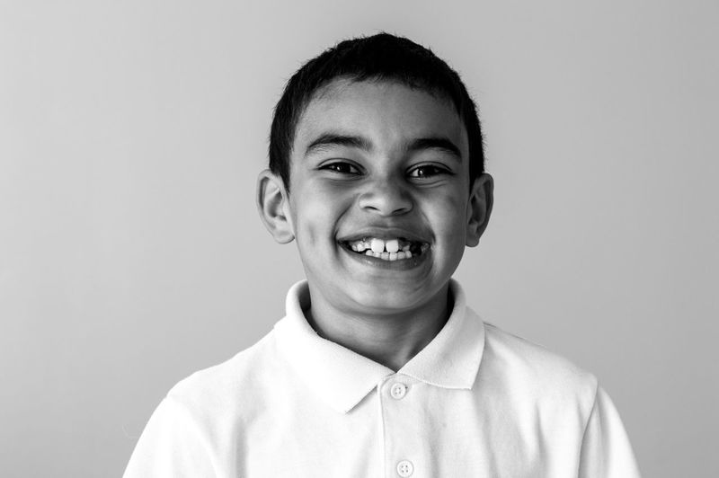 Close-up portrait of smiling boy over white background