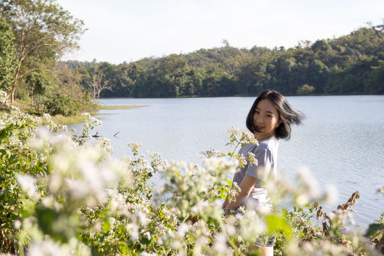 Portrait of young woman standing by plants at lakeshore in forest