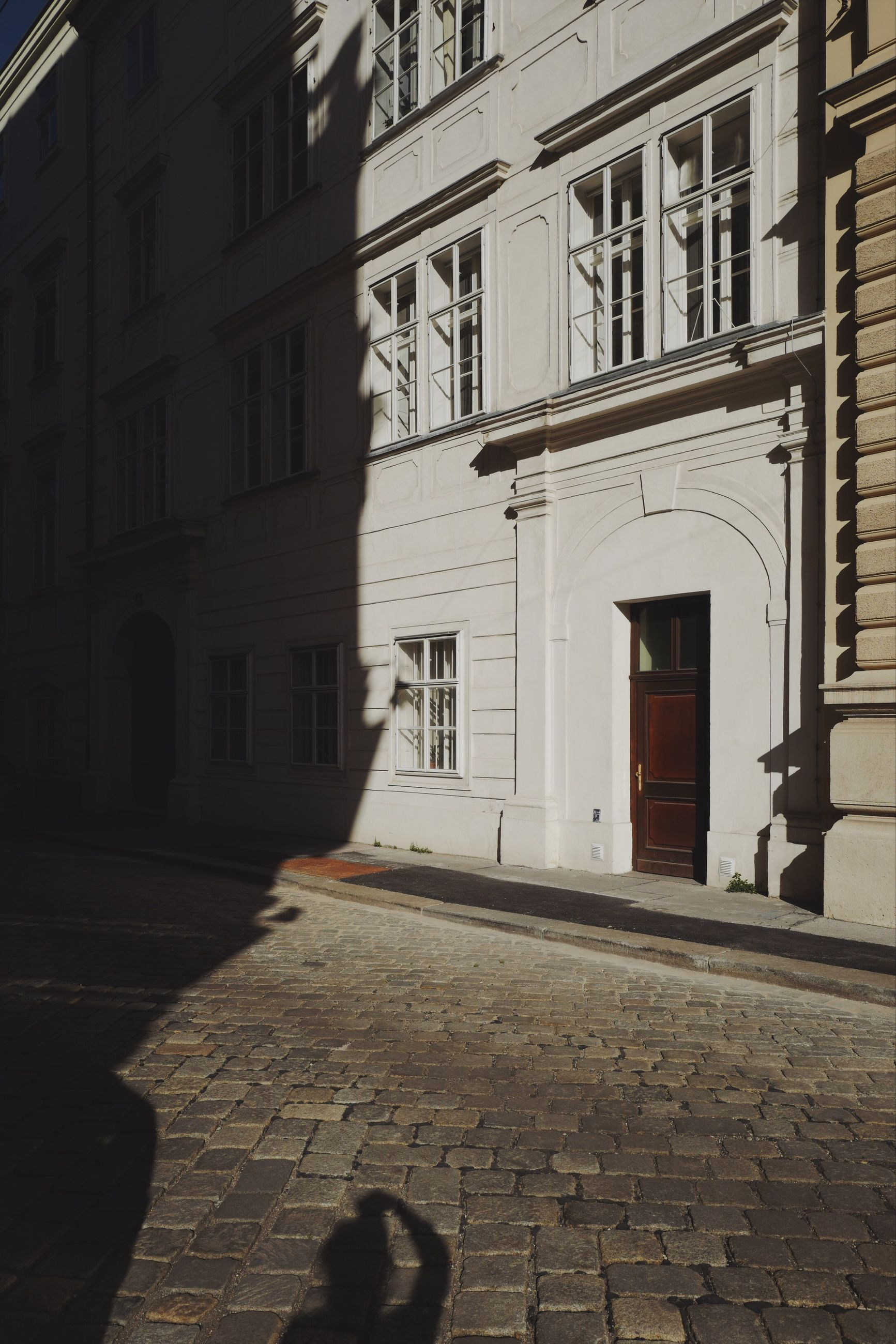 built structure, architecture, building exterior, building, city, street, day, residential district, window, sunlight, shadow, footpath, no people, outdoors, cobblestone, nature, entrance, door
