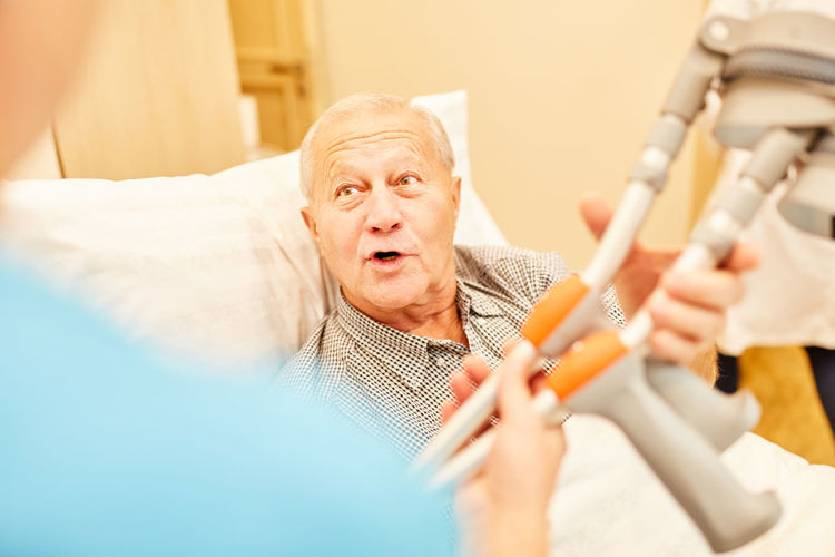 Senior man talking with healthcare worker while holding crutch at nursing home
