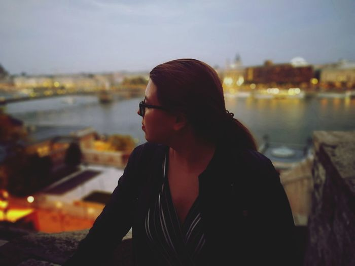 Portrait of young woman looking at cityscape against sky during sunset