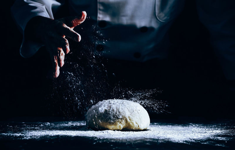 Midsection of chef sprinkling flour on dough at table in dark
