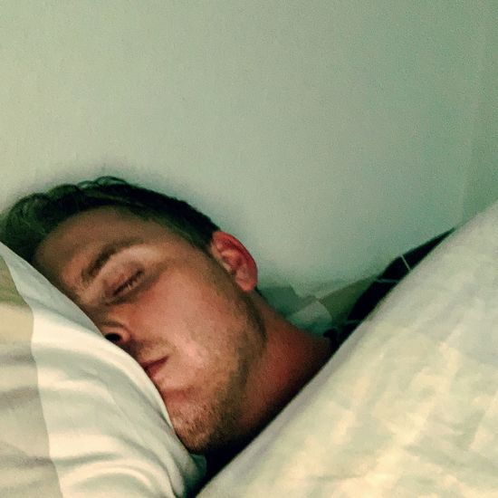 Portrait of young man sleeping on bed