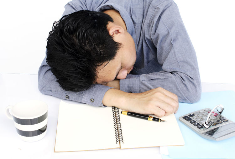 Portrait of frustrated man putting head down on desk against white background