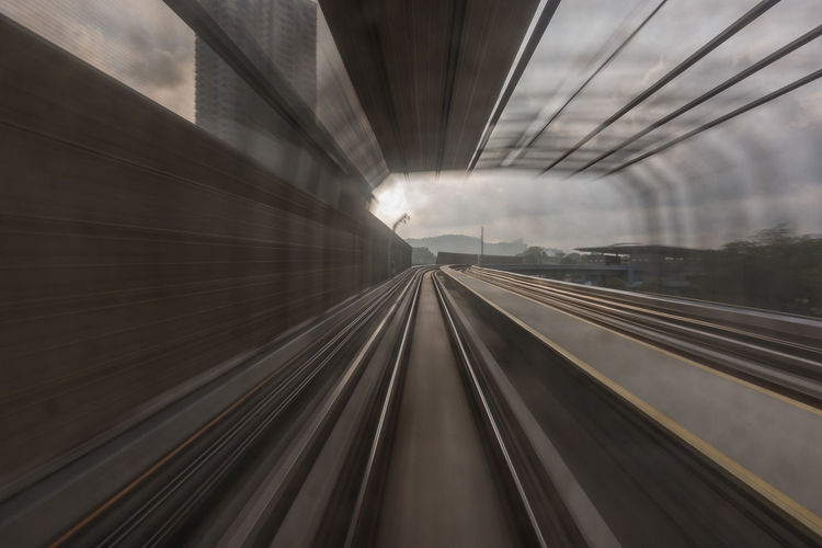 Blurred motion of railroad track in tunnel during sunset