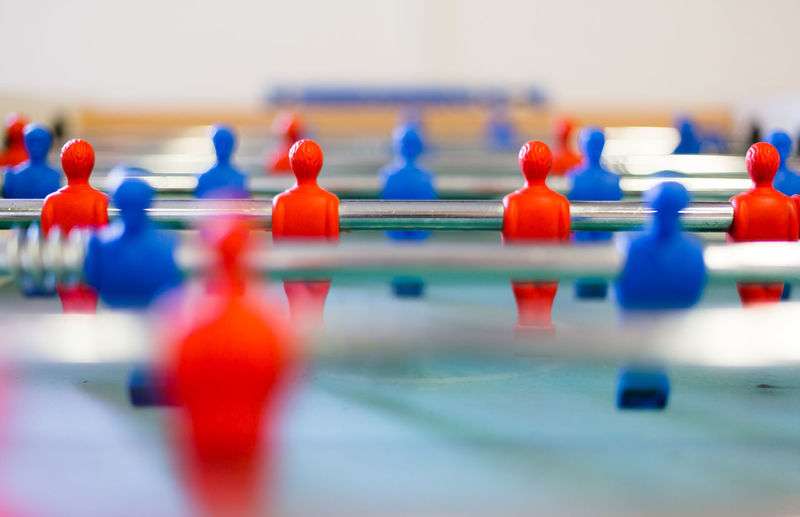 Table football, foosbal red and blue players in macro view. Low angle detailed view with selective focus and shallow depth of field. Banksters Blue Challenge Close-up Competition Control Controlled People Credit Tied Crowd Crowded Depended People Dependency Dividing Follower Foosball Fusball In A Row Networking Order Polls Red Selective Focus Still Life Teamwork Tied