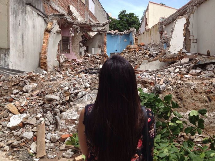 Rear view of woman standing in front of damaged building