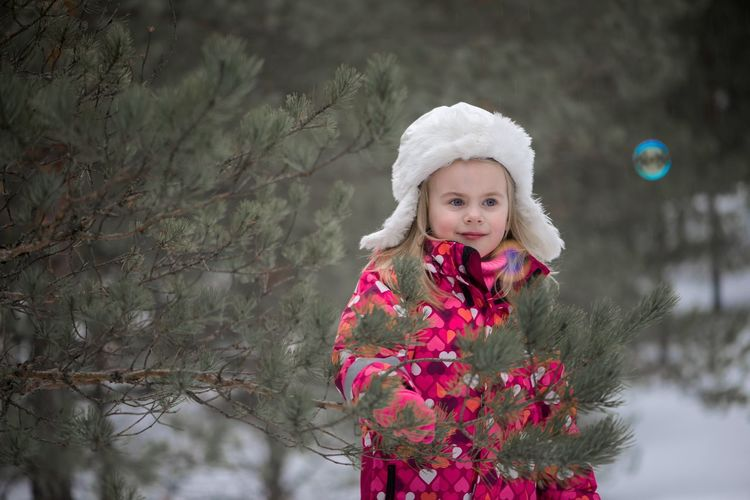 Girl Smiling While Standing By Trees