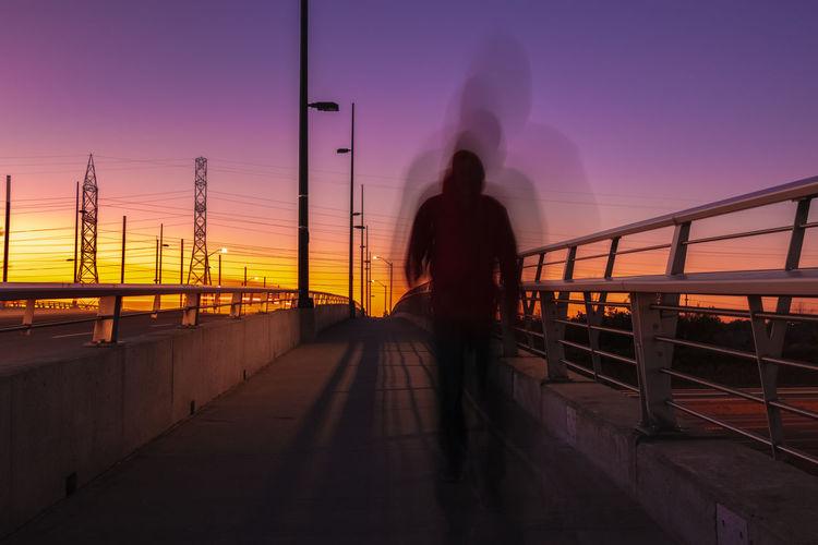 Blurred motion of man walking on bridge against sky during sunset