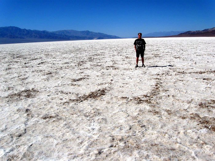 Man Standing At Badwater Basin In Death Valley National Park