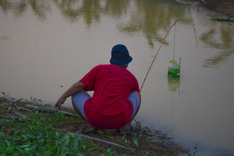 Rice field Rice Field Water Real People Rear View One Person Men Sitting Lake Full Length Casual Clothing Crouching Fishing Lifestyles Nature Clothing Leisure Activity Day Hat Activity Outdoors Hood - Clothing Warm Clothing