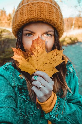 Portrait of woman holding maple leaf
