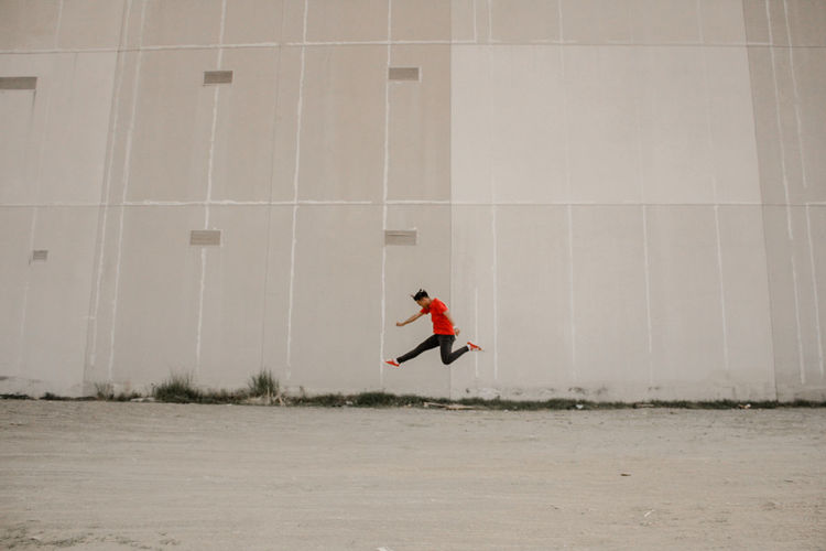 Side View Of Man Jumping Over Ground Against Building