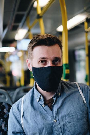Portrait of man wearing mask in train