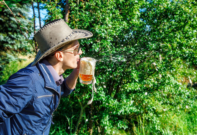 Side view of young man blowing froth from beer glass against plants