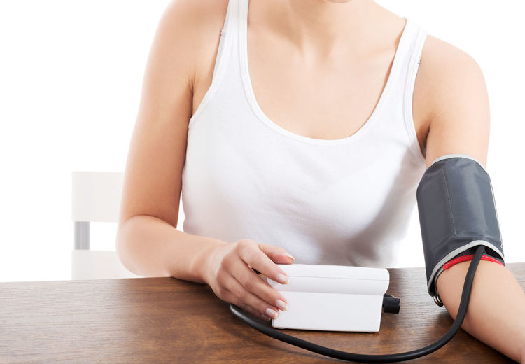 Midsection of woman checking blood pressure on table against white background