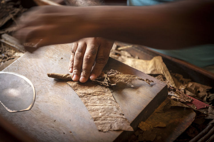 A craftsman works on hand rolling cigars in Santo Domingo, Dominican Republic Adult Caribbean Cigar Close-up Craftsperson Day Dominican Republic Expertise Human Body Part Human Hand Indoors  Making One Person People Preparation  Real People Santo Domingo Skill  Smoking Unrecognizable Person Working Workshop
