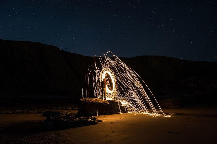 Man standing by wire wool at beach against sky