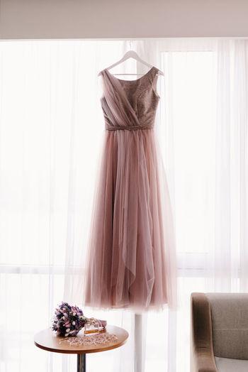 Wedding dress hanging on coat hanger against white curtain