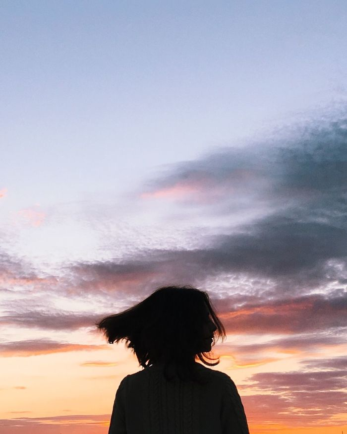 Rear view silhouette of woman tossing hair while standing against sky during sunset