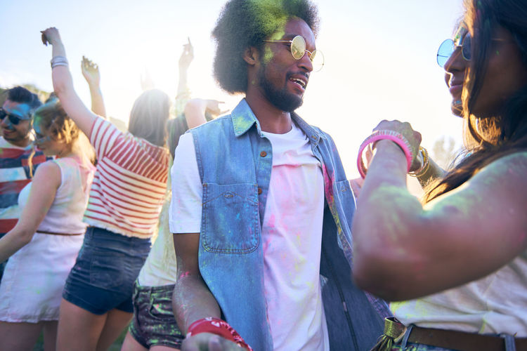 Colorful man during the festival Festival Colors Friends Dance Music Festival Summer Party Fun Holi African American People Traditional Festival Group Of People Traveling Carnival Outdoors African African American Popular Music Concert Music Multi Colored Powder Paint Face Paint Adult Crowd Coachella Valley Celebration Freedom Carefree Hinduism Holiday Vacations Youth Culture Togetherness Live Event Fashion Fashionable Sunglasses Arts Culture And Entertainment Bond Positive Emotion Enjoyment Close Up on the move