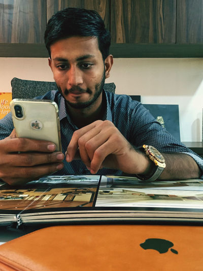 Portrait of young man using smart phone while sitting on table