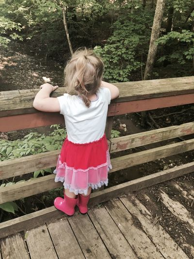 High angle view of girl standing on wooden railing