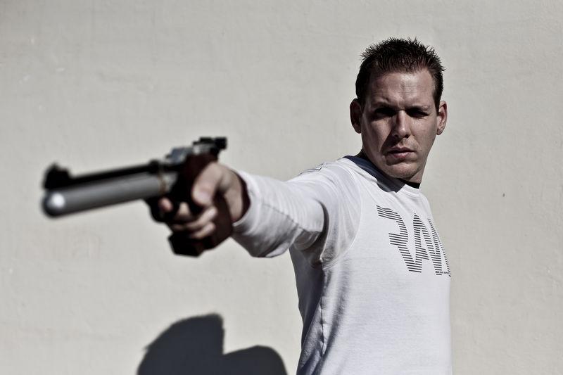 Man aiming gun while standing against wall